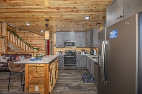Stainless appliances in a kitchen with gray cabinets at Allstar Pool Lodge, a 4 bedroom cabin rental located in Pigeon Forge
