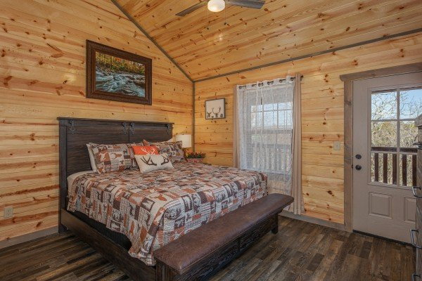Bedroom with king bed, bench, and deck access at Allstar Pool Lodge, a 4 bedroom cabin rental located in Pigeon Forge