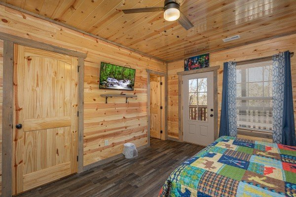 TV and deck access in a bedroom at Allstar Pool Lodge, a 4 bedroom cabin rental located in Pigeon Forge