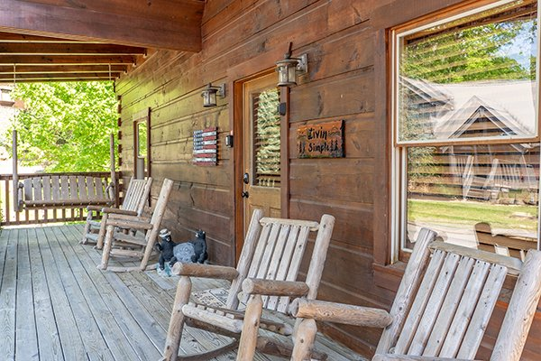Rocking chairs on a covered deck at Livin' Simple, a 2 bedroom cabin rental located in Pigeon Forge