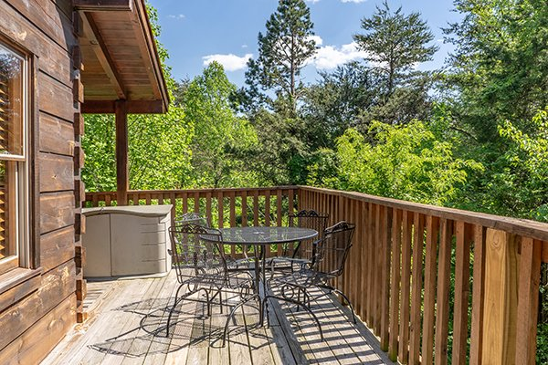 Dining table for 4 on an open deck at Livin' Simple, a 2 bedroom cabin rental located in Pigeon Forge