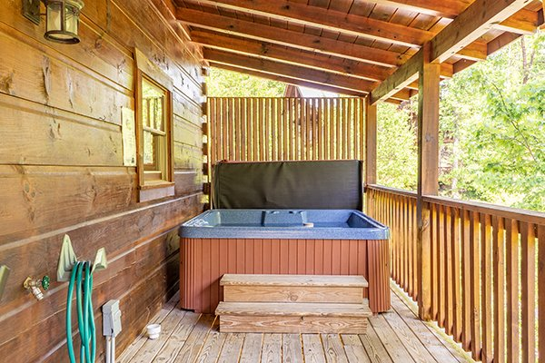 Hot tub on a covered deck at Livin' Simple, a 2 bedroom cabin rental located in Pigeon Forge