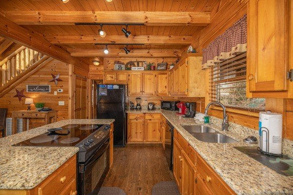 Kitchen with granite counters and black appliances at Livin' Simple, a 2 bedroom cabin rental located in Pigeon Forge