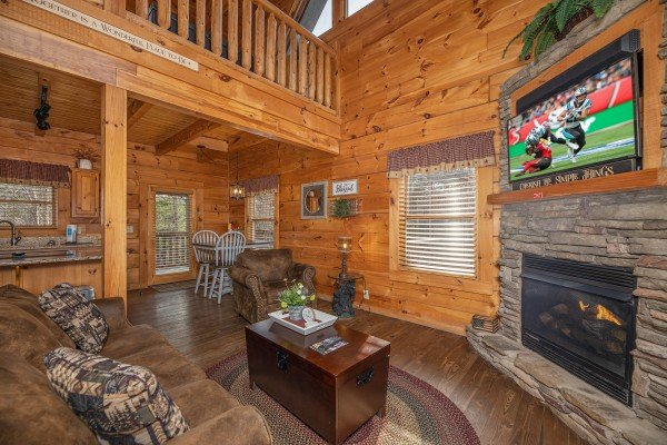 Living room with fireplace & TV, dining space, and adjacent kitchen at Livin' Simple, a 2 bedroom cabin rental located in Pigeon Forge