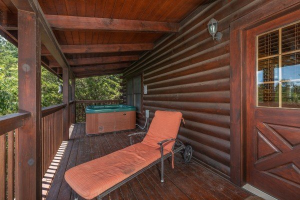 Chaise lounge and hot tub on a covered deck at Top of the Way, a 2 bedroom cabin rental located in Pigeon Forge