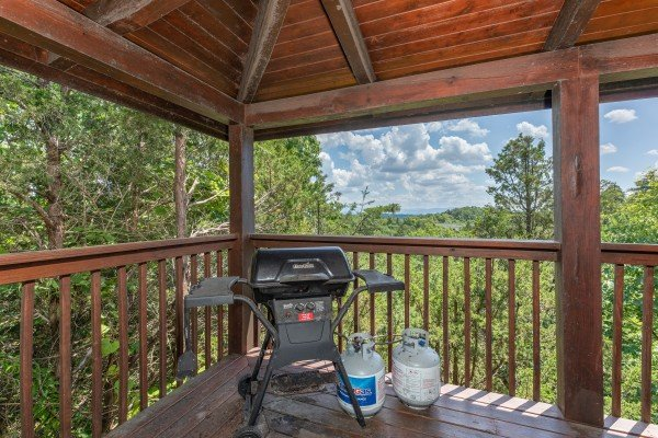 Gas grill on a covered deck at Top of the Way, a 2 bedroom cabin rental located in Pigeon Forge