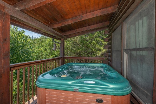 Hot tub on a covered deck at Top of the Way, a 2 bedroom cabin rental located in Pigeon Forge