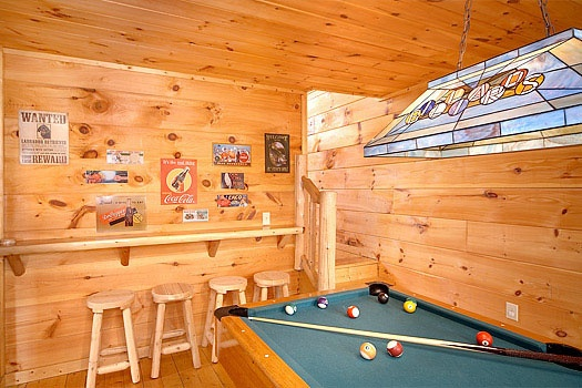 bar stools behind the pool table with shelving ledge at american dream a 2 bedroom cabin rental located in gatlinburg