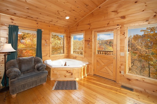 jacuzzi tub in the corner of the master bedroom at american dream a 2 bedroom cabin rental located in gatlinburg
