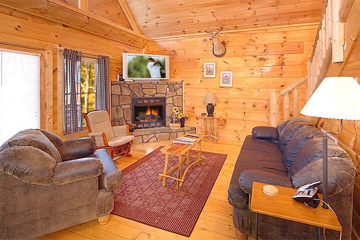 a fireplace and sofa bed in the living room of american dream a 2 bedroom cabin rental located in gatlinburg