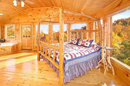 master bedroom large king sized bed with many windows to allow natural light through at american dream a 2 bedroom cabin rental located in gatlinburg