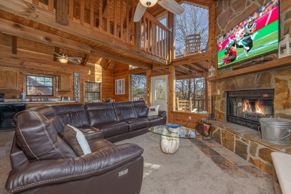 Living room with fireplace and TV at Eagle Watch Den, a 5 bedroom cabin rental located in Pigeon Forge
