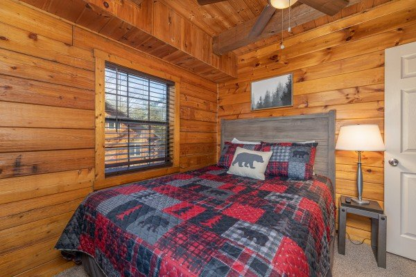 Bedroom with a lamp and table at Eagle Watch Den, a 5 bedroom cabin rental located in Pigeon Forge