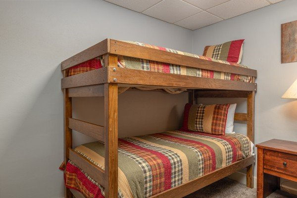 Bunk room with nightstand and lamp at Eagle Watch Den, a 5 bedroom cabin rental located in Pigeon Forge