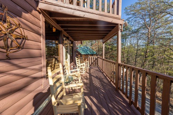 Deck with rocking chairs at Eagle Watch Den, a 5 bedroom cabin rental located in Pigeon Forge