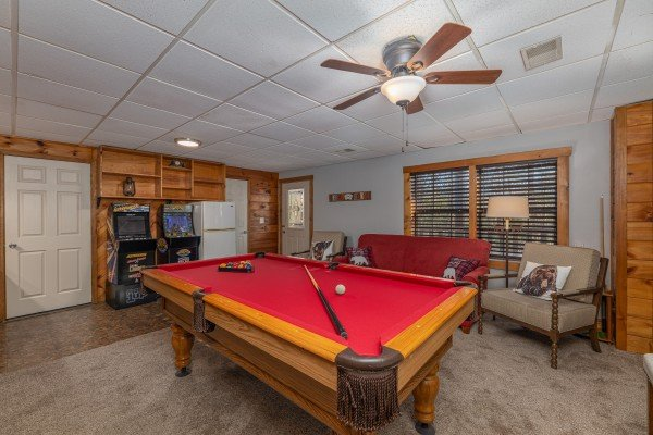 Red felt pool table and video games in a game room at Eagle Watch Den, a 5 bedroom cabin rental located in Pigeon Forge