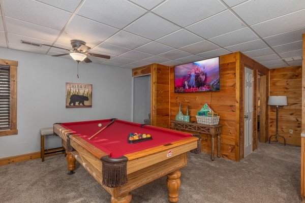 Pool table and TV in the game room at Eagle Watch Den, a 5 bedroom cabin rental located in Pigeon Forge