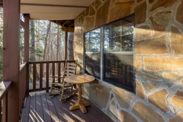 Rocking chair and table on a deck at Eagle Watch Den, a 5 bedroom cabin rental located in Pigeon Forge