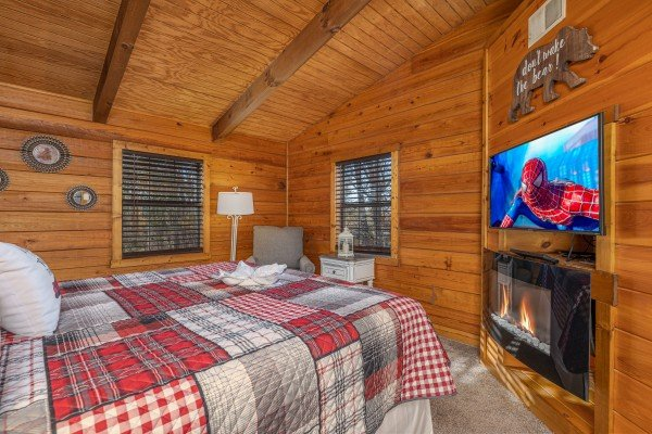 Bedroom with a TV and fireplace at Eagle Watch Den, a 5 bedroom cabin rental located in Pigeon Forge