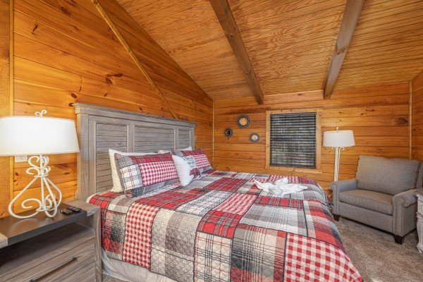 Bedroom with night stand, lamps, and chair at Eagle Watch Den, a 5 bedroom cabin rental located in Pigeon Forge