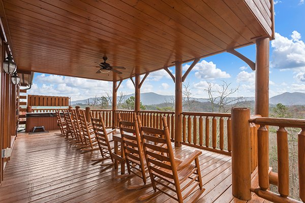 Rocking chairs lined up on a covered deck overlooking the mountains at Grand Timber Lodge, a 5-bedroom cabin rental located in Pigeon Forge