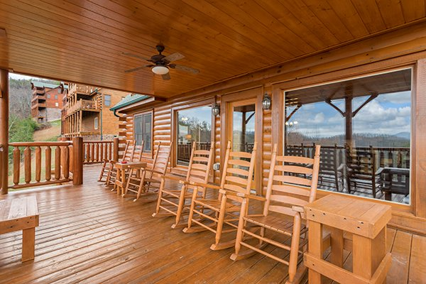 Rocking chairs on a covered deck overlooking the winter views at Grand Timber Lodge, a 5-bedroom cabin rental located in Pigeon Forge