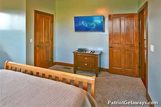 Third floor bedroom with flat screen mounted to wall at Grande Mountain Lodge, a 5-bedroom cabin rental located in Pigeon Forge