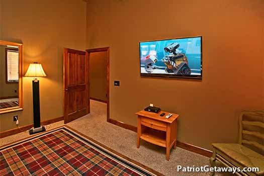 large flat screen on the wall in the first floor bedroom at grande mountain lodge a 5 bedroom cabin rental located in pigeon forge