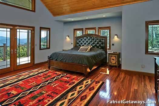 main floor bedroom with king sized bed at grande mountain lodge a 5 bedroom cabin rental located in pigeon forge