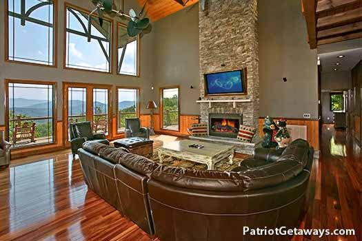Luxury living room with large leather sectional sofa at Grande Mountain Lodge, a 5-bedroom cabin rental located in Pigeon Forge