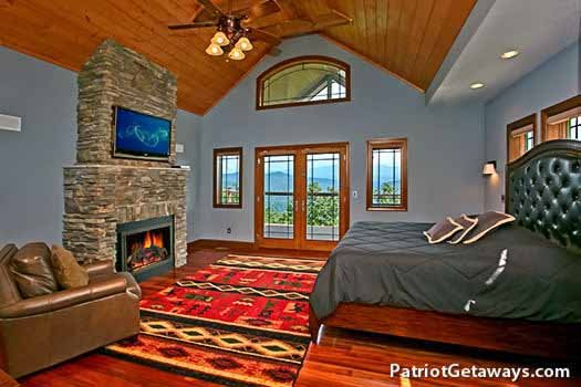 Main floor bedroom with fireplace at Grande Mountain Lodge, a 5-bedroom cabin rental located in Pigeon Forge