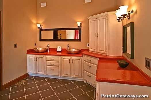 Main floor bathroom with his and hers bowl sinks and custom cabinetry at Grande Mountain Lodge, a 5-bedroom cabin rental located in Pigeon Forge