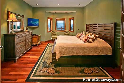 king sized bed on main floor bedroom at grande mountain lodge a 5 bedroom cabin rental located in pigeon forge
