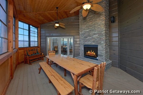 Large dining space on an enclosed patio with a fireplace at Grande Mountain Lodge, a 5-bedroom cabin rental located in Pigeon Forge