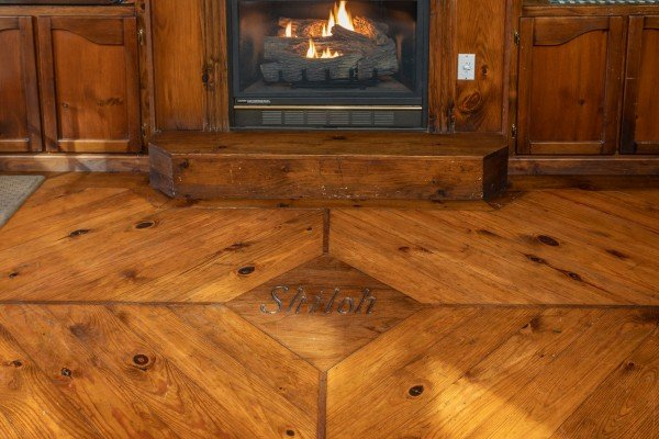 Custom flooring inlay in front of the living room fireplace at Shiloh, a 3 bedroom cabin rental located in Gatlinburg