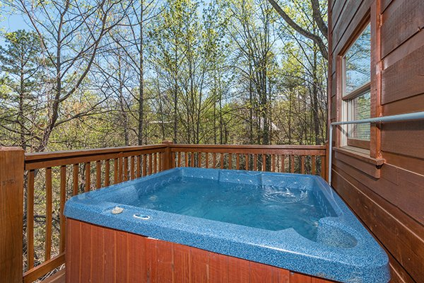 Hot tub on the deck surrounded by woods at Lumber Jack Lodge, a 1 bedroom cabin rental located in Gatlinburg