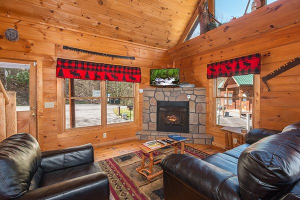 Living room corner fireplace and TV at Lumber Jack Lodge, a 1 bedroom cabin rental located in Gatlinburg