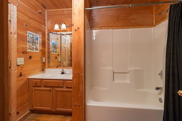 Bathroom with a tub and shower at Lumber Jack Lodge, a 1 bedroom cabin rental located in Gatlinburg