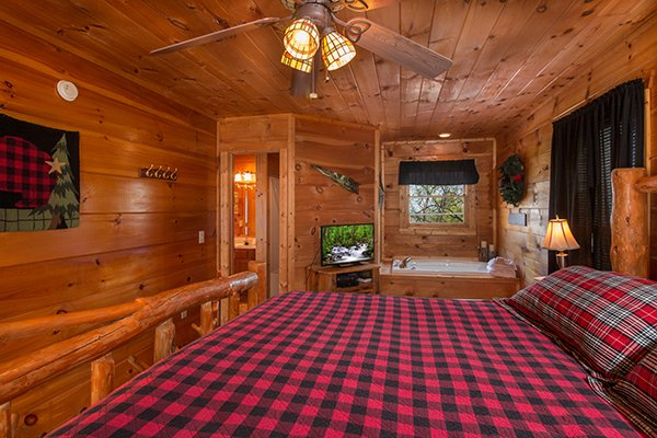 Bedroom with a TV and jacuzzi tub at Lumber Jack Lodge, a 1 bedroom cabin rental located in Gatlinburg