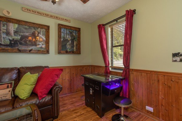 Arcade game in the living room at Bear Mountain Hollow, a 1 bedroom cabin rental located in Pigeon Forge
