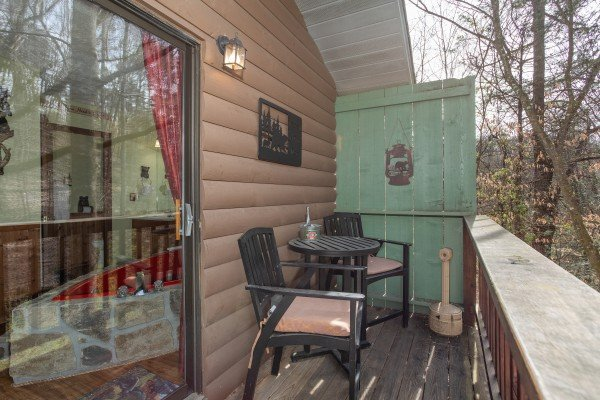 Sitting area with table and chairs on the deck at Bear Mountain Hollow, a 1 bedroom cabin rental located in Pigeon Forge