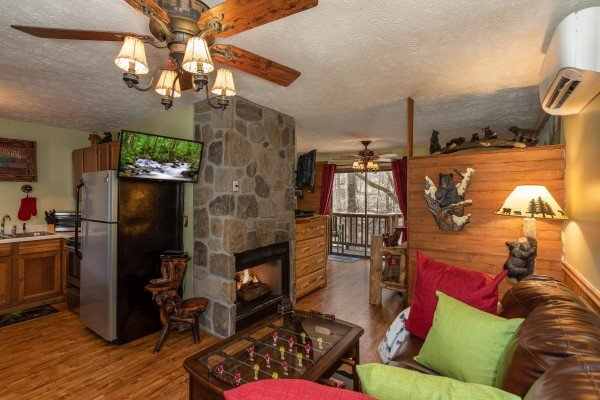 TV, foosball coffee table, and fireplace in the living room at Bear Mountain Hollow, a 1 bedroom cabin rental located in Pigeon Forge