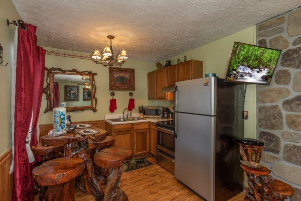 Kitchen with stainless appliances and dining space for four at Bear Mountain Hollow, a 1 bedroom cabin rental located in Pigeon Forge