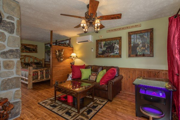 Sleeper sofa and arcade game in the living room at Bear Mountain Hollow, a 1 bedroom cabin rental located in Pigeon Forge