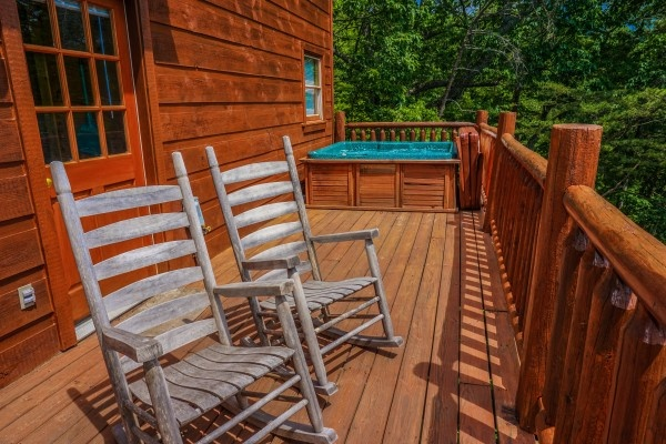 rockers and a hot tub on the back deck at deerly beloved a 1 bedroom cabin rental located in gatlinburg