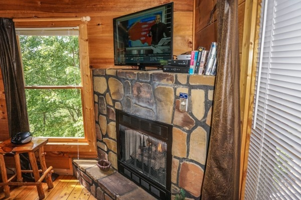 flat screen tv above the stone fireplace at deerly beloved a 1 bedroom cabin rental located in gatlinburg