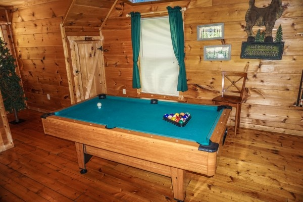 Pool table in the lofted game room at Deerly Beloved, a 1-bedroom cabin rental located in Gatlinburg