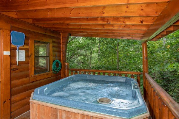 Hot tub on a covered deck surrounded by woods at Dreams Do Come True, a 1-bedroom cabin rental located in Pigeon Forge