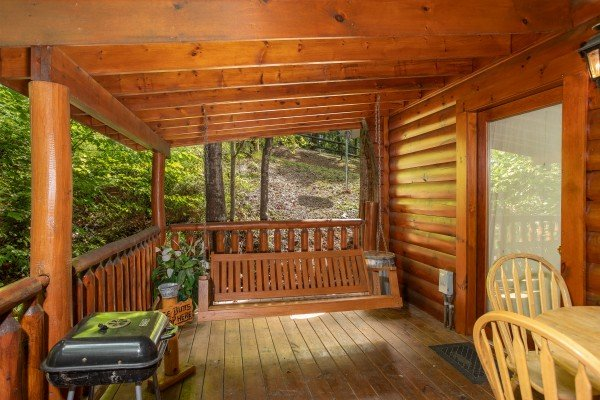 Covered porch with swing, dining space, and a charcoal grill at Dreams Do Come True, a 1-bedroom cabin rental located in Pigeon Forge