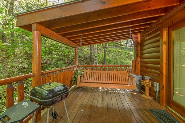 Charcoal grill and a covered porch swing at Dreams Do Come True, a 1-bedroom cabin rental located in Pigeon Forge